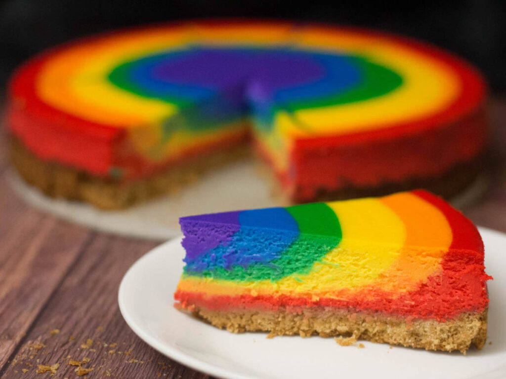 one slice of rainbow cheesecake in front of the rest of the cheesecake