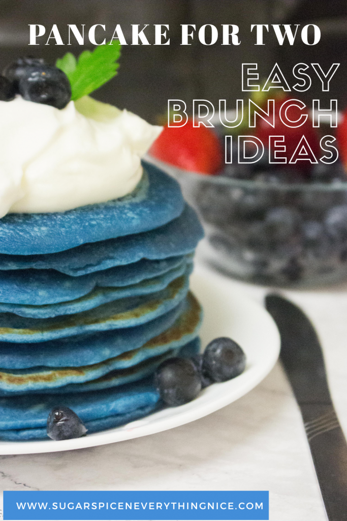 Blue pancake stack with whipped cream and blueberries. Bowl of strawberries and blueberries in the background. Pinable image of pancake for two recipe