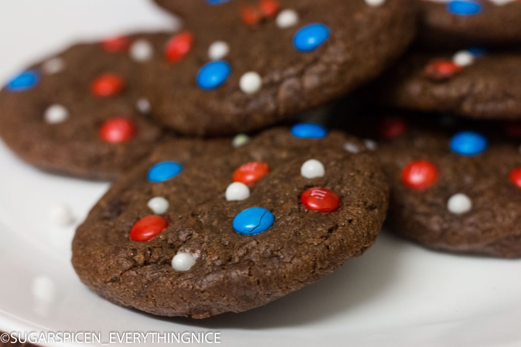 Close up of a single chocolate cookies with Red, Blue and White MnMs
