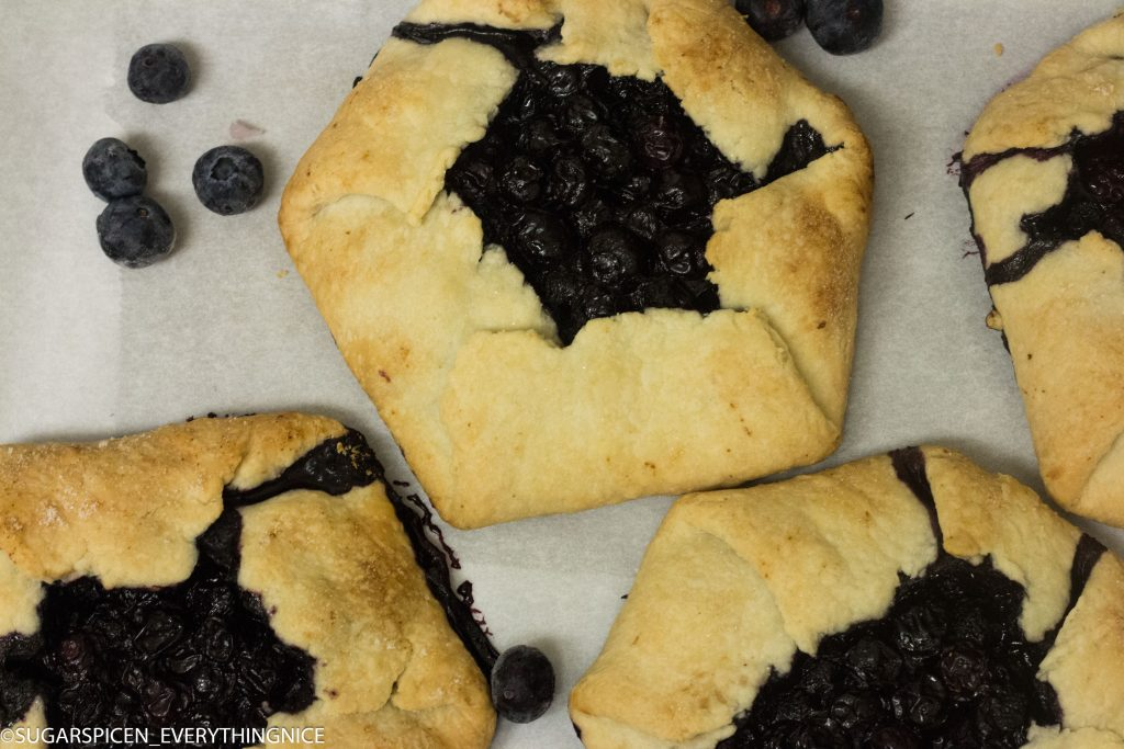 3 blueberry galettes with few blueberry around it placed on white marble countertop.