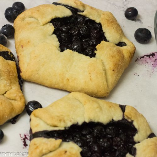 3 mini blueberry galettes with blueberries around