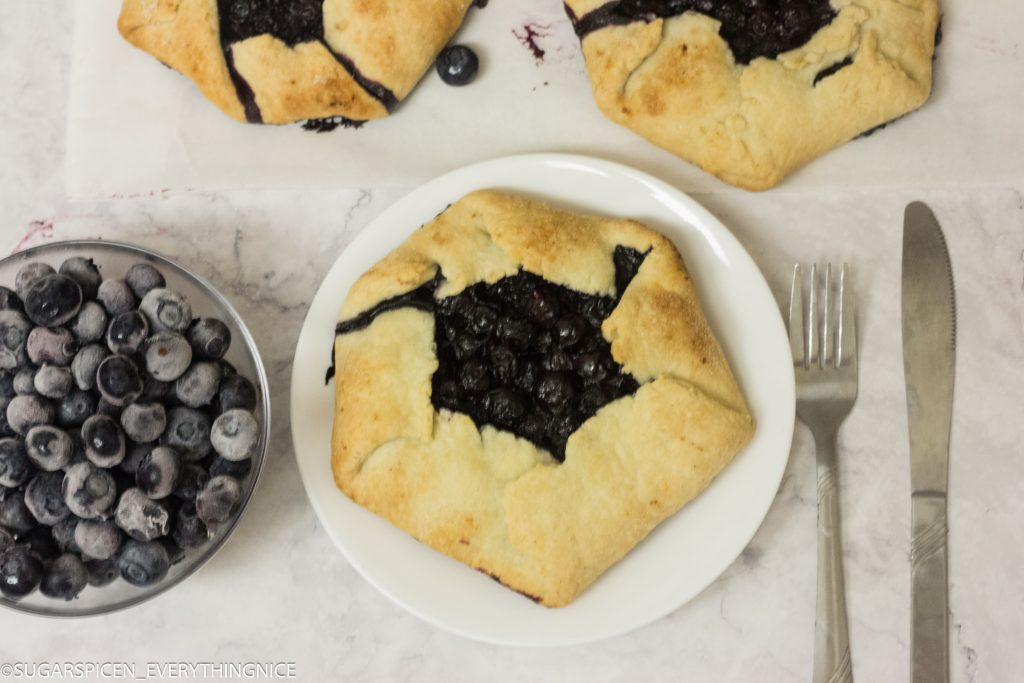 3 blueberry galettes with few blueberries kept on a bowl.