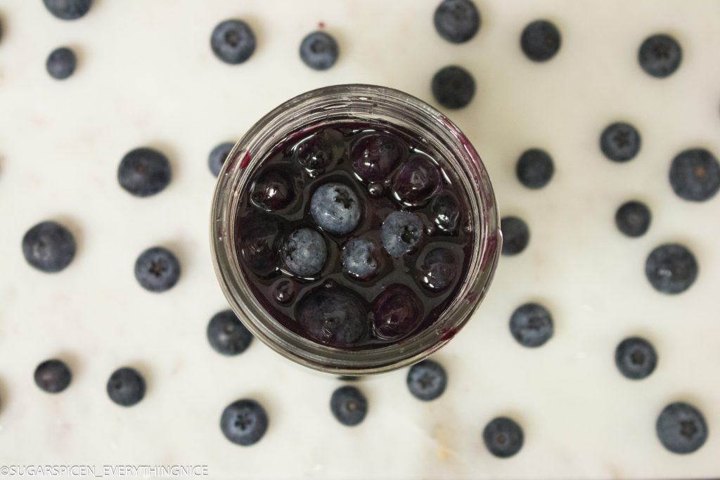 Top view of blueberry topping sauce and lot of blueberries around it