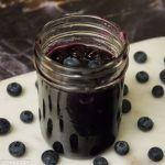 Blueberry topping sauce in a mason jar and lot of blueberries around it