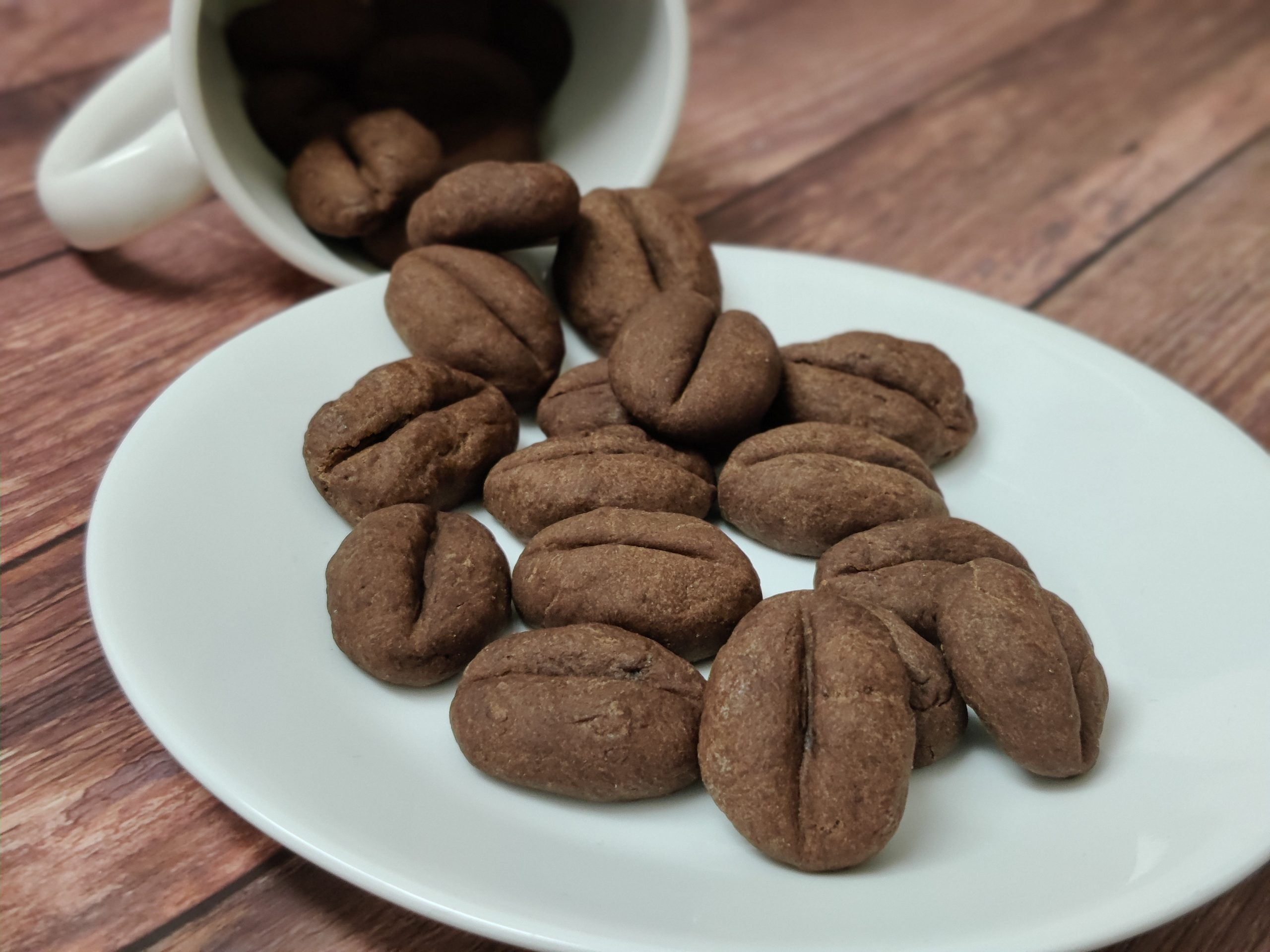 Coffee bean cookies pouring out from white coffee mug on to a white plate