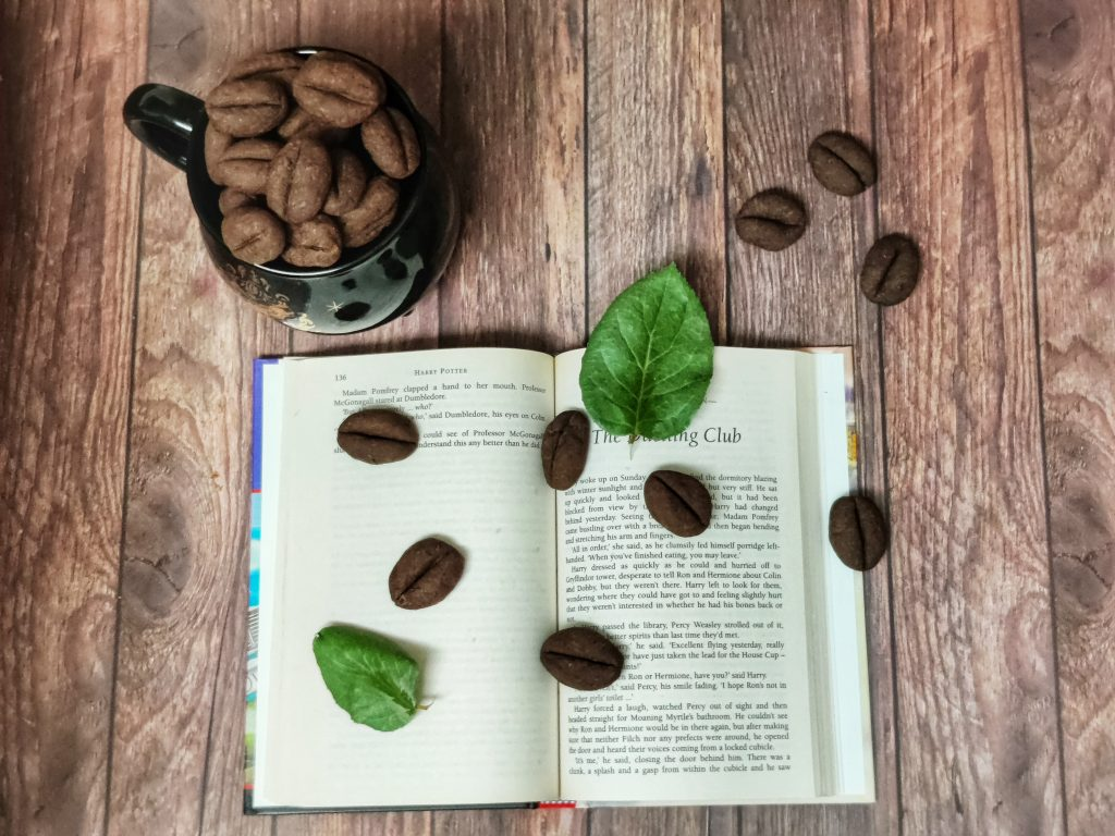 Coffee bean cookies piled up on black coffee mug next to an open book sprinkled with few coffee bean cookies and two green leaves on a wooden table