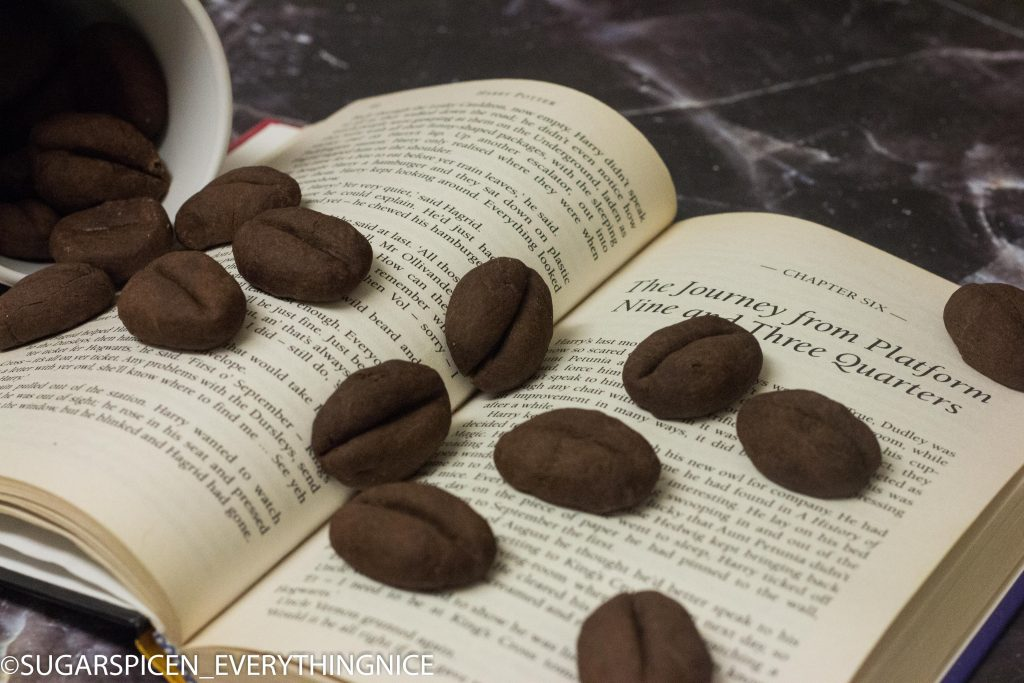 Coffee bean cookies falling out from a white coffee mug on to an open book