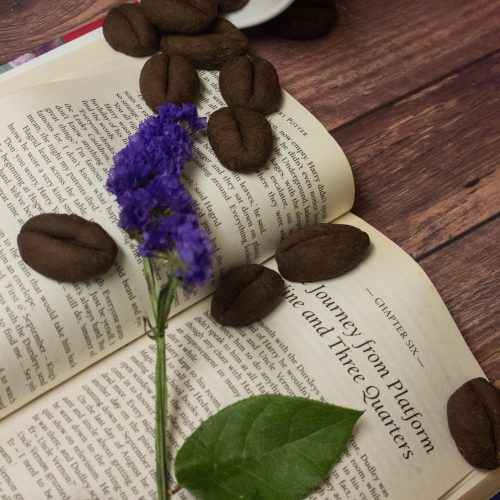 Coffeebean cookie spilling out of a cup onto a book