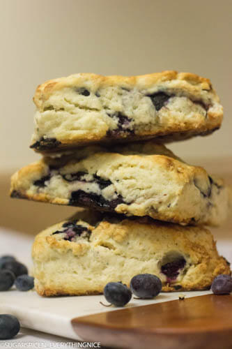 3 starbucks blueberry scones kept one on top of the other with blueberry spread around it.