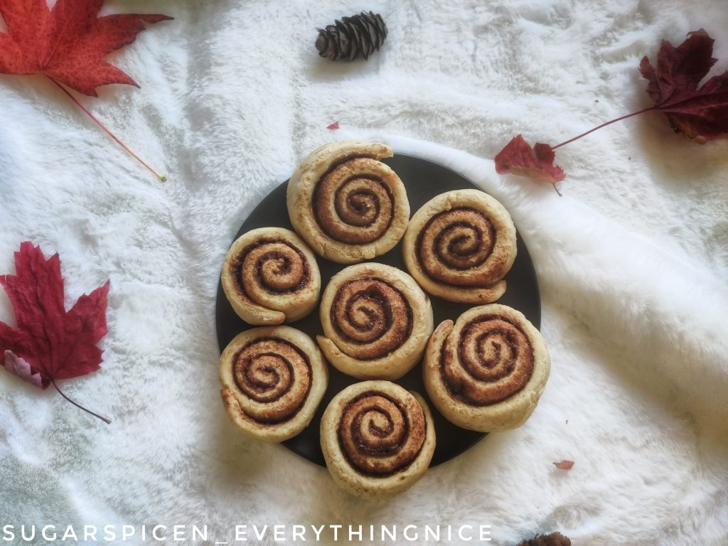 A plate of cinnamon rolls with fall leaves around