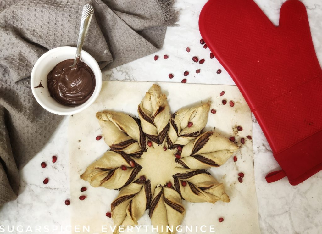 baked star bread with pomegranite seeds over it. A side of vegan chocolate spread and a red oven mitt kept on the side.