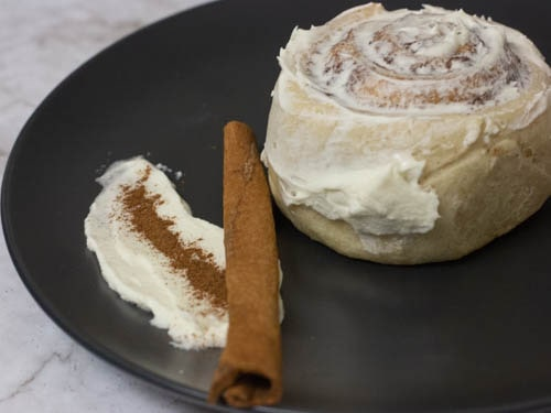 dairy free cinnamon roll with cream cheese frosting with a cinnamon stick on the side