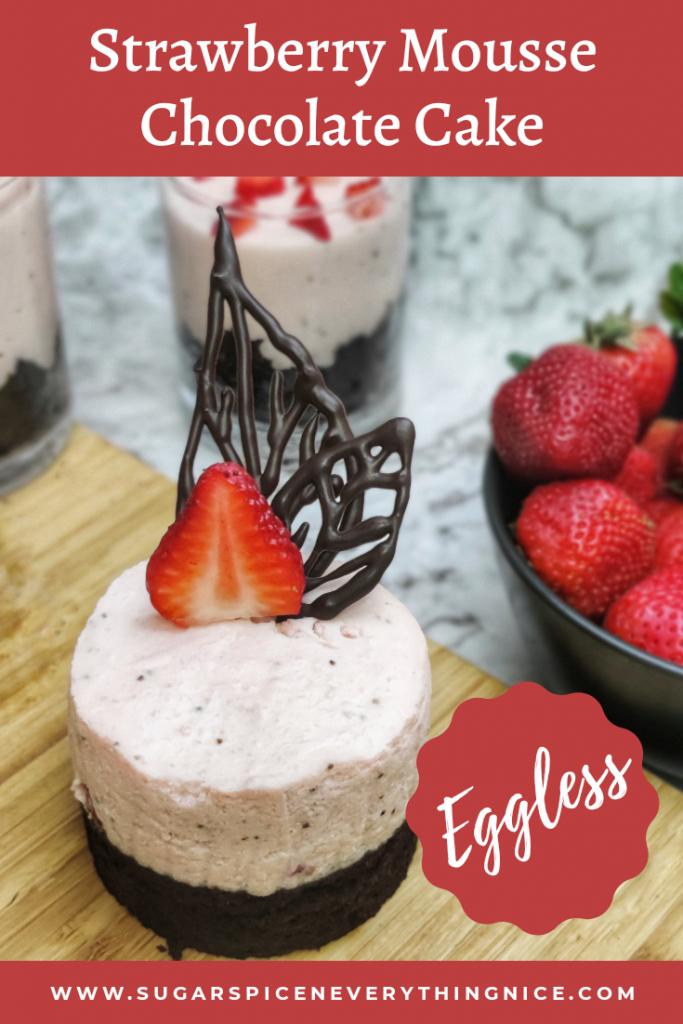 Strawberry Mousse Chocolate with solid design embedded in it. It is kept on a cutting board surrounded with strawberries.