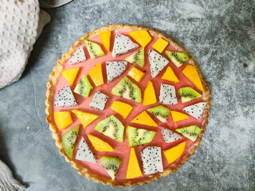 Custard fruit tart with kiwi, dragon fruit and mango arranged in a geometric puzzle pattern over cranberry jelly.