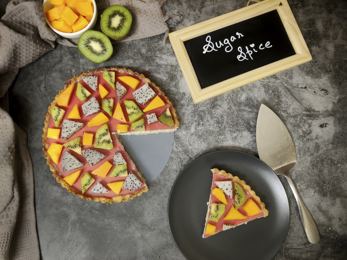 """Custard fruit tart with kiwi, dragon fruit and mango arranged in a geometric puzzle pattern over cranberry jelly. A slice is cut from it. Cut mango and kiwi kept on the side as well as a chalkboard with """" Sugar Spice"""" written on it."""