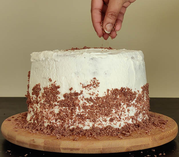 adding chocolate shavings halfway up the cake and on top