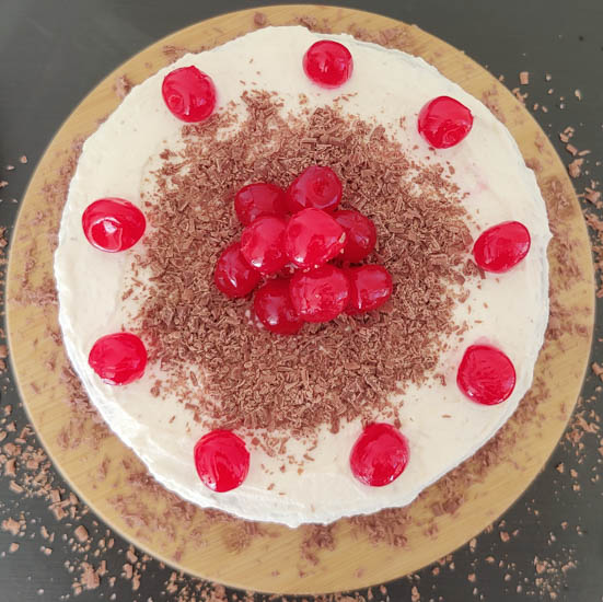decorate the cake with cherries and chocolate shavings