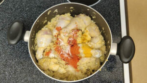 marinated chicken and spices added to the pot