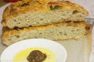 Cut Focaccia bread with air pocket. Herb and olive oil mixture kept in front.