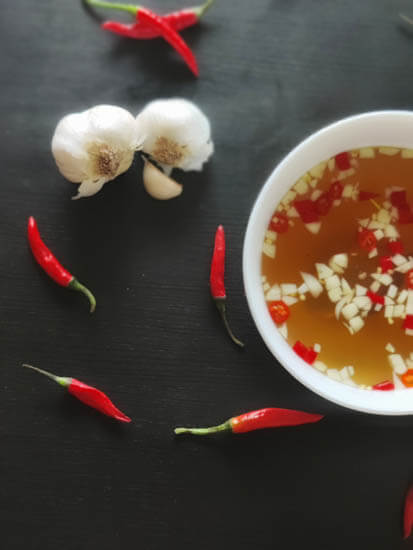 nuoc mam in a bowl with chilis and garlic around it