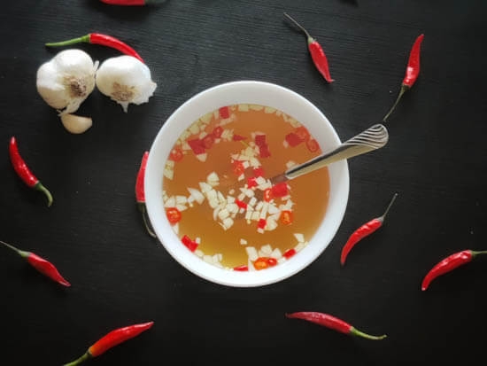 nuoc mam in a bowl with chilis around it