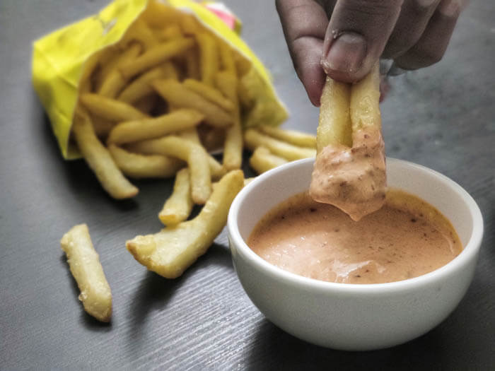 subway chipotle sauce in a small bowl surrounded by chicken wings and french fries. Fries are dipped in this southwest sauce