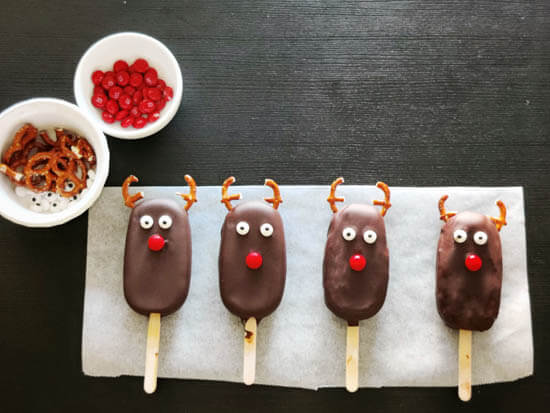 chocolate coated ice cream bars, decorated as reindeers are kept in a line