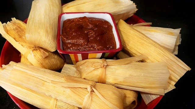 tamales kept on a plate around a cup of salsa