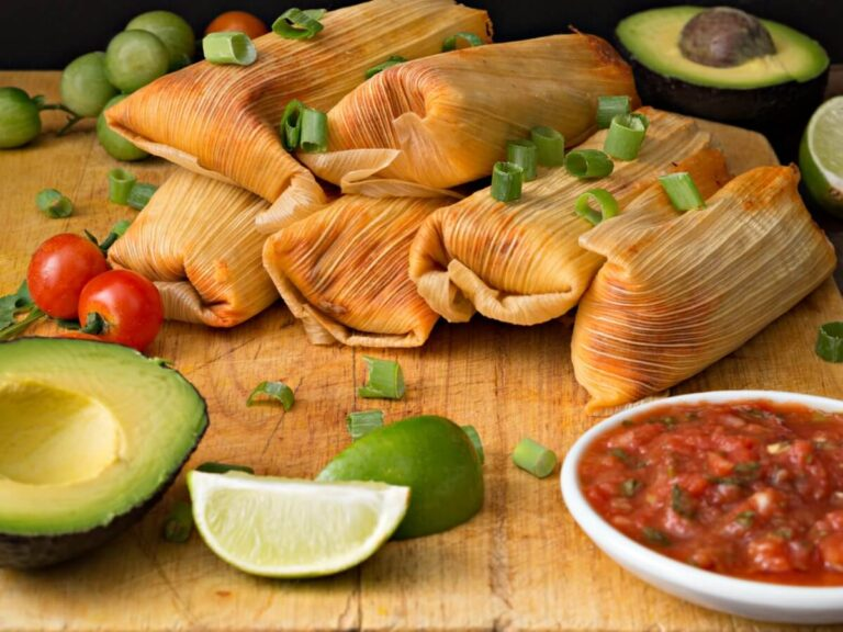 6 tamales kept on a table with avocado and salsa kept on the side