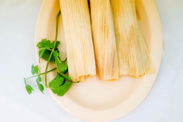 4 tamales with husk kept on a plate
