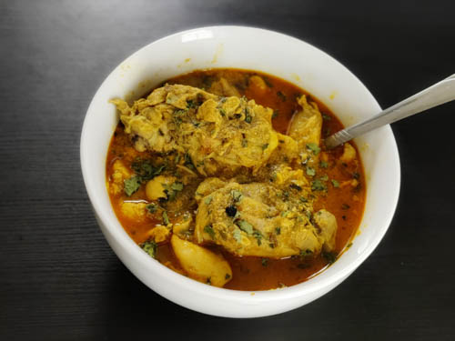 chicken salan recipe in a white bowl with a spoon