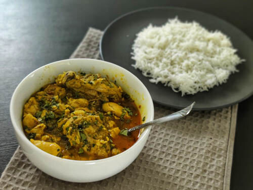 chicken salan recipe in a white bowl with a spoon with a side of white rice