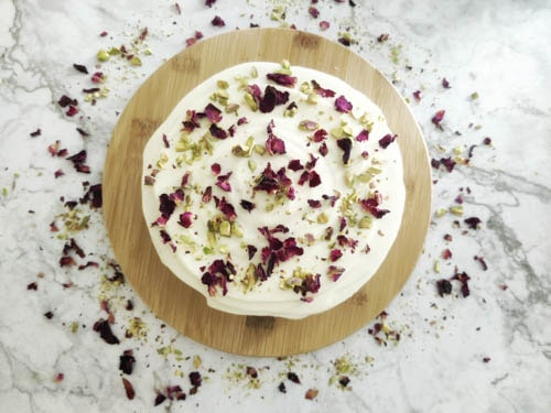 ras malai cake with frosting decorated with rose petals and pistachios