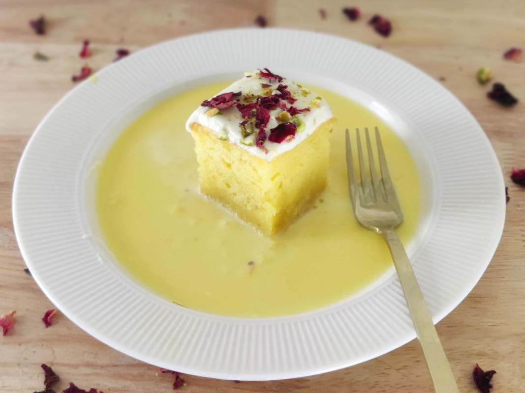 rasmalai cake slice kept on a plate with ras milk around it and a fork kept near it