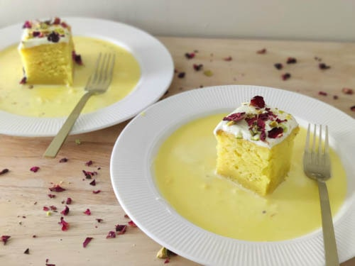 2 rasmalai cake slices kept on couple of plates with ras milk around it and a fork kept near it
