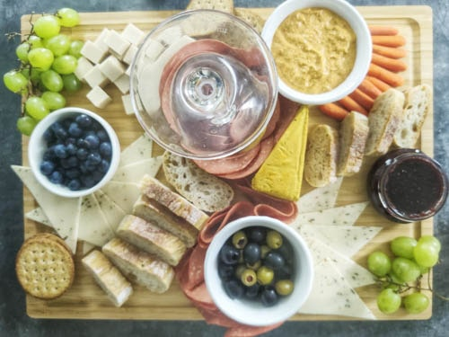 adding fruits, bread and crackers to the board