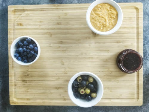 add bowls of blueberries, hummus, olives and raspberry jam